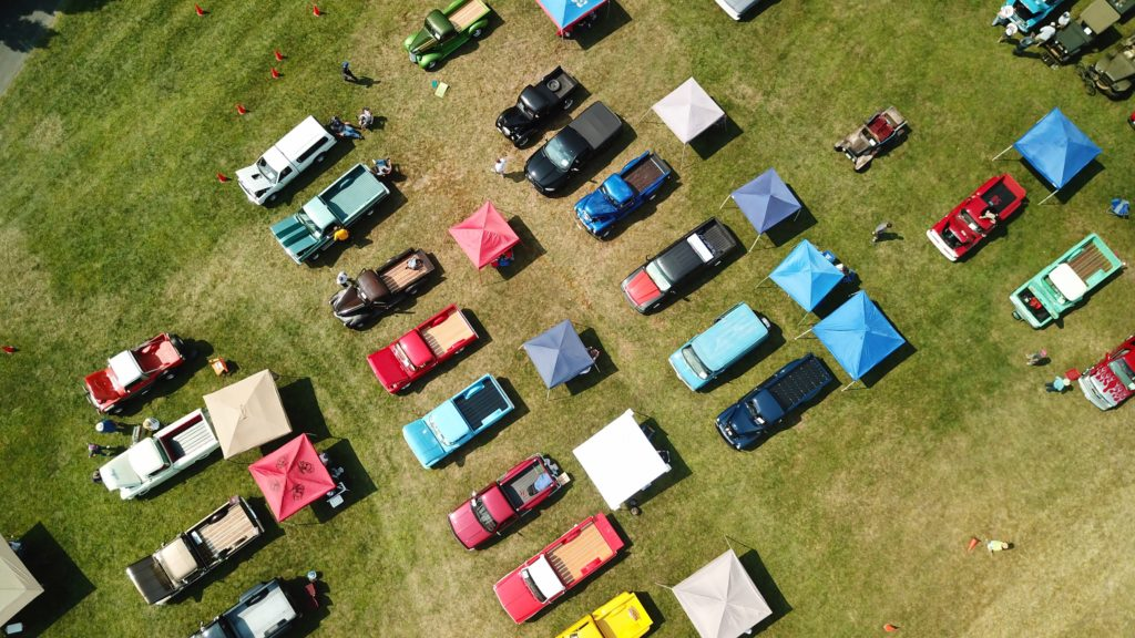 trucks in a grass field for a truck show